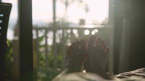 Pés desencapados que dançam na cama no amanhecer no sol com efeitos bonitos do alargamento da lente Movimento lento 3840x2160 filme