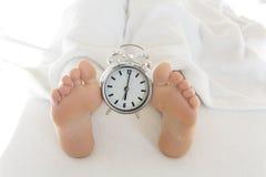 Pés despidos na cama com despertador Fotos de Stock Royalty Free