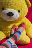 Pés do adolescente com um urso de peluche no fundo Fotos de Stock Royalty Free