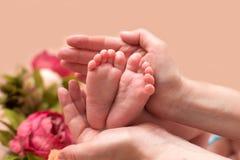 Pés do bebê colocados nas mãos das mães Imagens de Stock