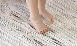 Pés do bebê em um fundo de madeira branco que aprende imagens de stock royalty free