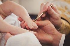 Pés do bebê na mão do ` s do paizinho christening fotografia de stock royalty free