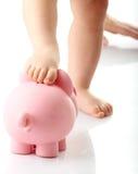 Pés do bebê no banco piggy Fotografia de Stock Royalty Free