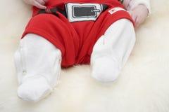 Pés do bebê no traje de Papai Noel Fotografia de Stock