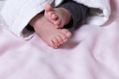 Pés do bebê para fora debaixo da cobertura morna Foto de Stock