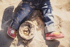 Pés do bebê pequeno, da menina na calças de ganga e das sapatas cor-de-rosa que sentam-se e que jogam na areia na praia Foto de Stock Royalty Free