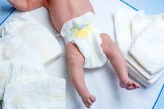 Pés do bebê recém-nascido na tabela em mudança com tecidos fotos de stock