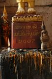 Pés do buddah do ouro com a estátua de assento do buddah Fotografia de Stock