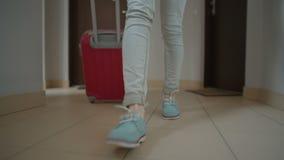 Pés do close up da senhora Leaving o apartamento e ir com a mala de viagem interna filme