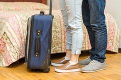 Pés do close up de calças de brim vestindo dos pares, estando ao lado da cama, mala de viagem azul no assoalho, conceito da pensã Fotos de Stock