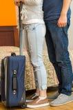 Pés do close up de calças de brim vestindo dos pares, estando ao lado da cama, mala de viagem azul no assoalho, conceito da pensã Fotografia de Stock
