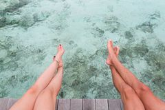 Pés do homem e da mulher assentados em um cais sobre a água azul clara imagens de stock royalty free