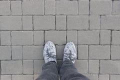 Pés do homem em blocos cinzentos do tijolo Fotos de Stock Royalty Free