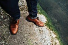 Pés do homem em calças de brim da ourela e em sapatas retros Foto de Stock