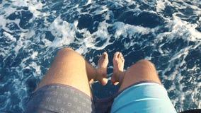 Pés do homem em um barco movente acima do mar vídeos de arquivo