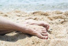 Pés do homem em uma praia Imagens de Stock Royalty Free