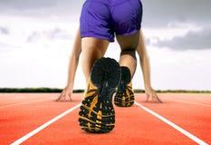 Pés do homem na pista de atletismo Imagens de Stock