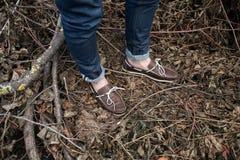 Pés do homem nas botas e nas calças de brim autênticas da ourela, no th Imagem de Stock Royalty Free