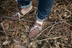 Pés do homem nas botas e nas calças de brim autênticas da ourela, no th Fotografia de Stock