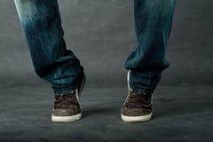 Pés do homem nas calças de brim Imagem de Stock