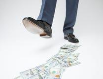 Pés do homem nas sapatas pretas que vão pela trilha do dinheiro Fotografia de Stock Royalty Free