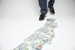 Pés do homem nas sapatas pretas que vão pela trilha do dinheiro Fotos de Stock