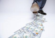 Pés do homem nas sapatas pretas que vão pela trilha do dinheiro Imagens de Stock