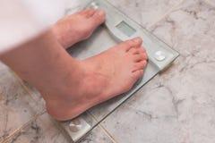 Pés do homem que estão na escala do peso Fotografia de Stock