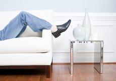 Pés do homem que reclinam no sofá branco fotografia de stock