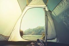 Pés do homem que relaxa apreciando montanhas e opinião do lago do verão exterior de acampamento da aventura do conceito do estilo fotografia de stock royalty free