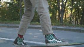 Pés do indivíduo do skater nas sapatilhas que fazem o truque em um skate fora Pés do indivíduo que patinam em um skate lento filme
