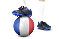 Pés do jogador de futebol com a bola no estúdio Fotografia de Stock