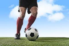 Pés do jogador de futebol em peúgas vermelhas e nas sapatas pretas que correm e que pingam com a bola que joga fora Imagem de Stock Royalty Free