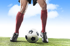 Pés do jogador de futebol em peúgas vermelhas e nas sapatas pretas que correm e que pingam com a bola que joga fora Fotografia de Stock
