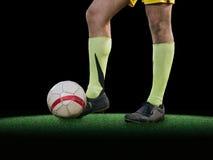 Pés do jogador de futebol que retrocedem a bola no fundo preto Fotografia de Stock