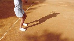 Pés do jogador de tênis no campo de tênis alaranjado da argila durante o jogo filme
