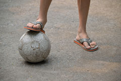 Pés do menino com esfera de futebol Fotos de Stock Royalty Free