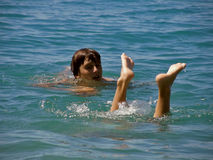 Pés do menino e da menina no mar Imagens de Stock