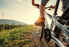 Pés do menino em sneackers vermelhos no fim do pedal da bicicleta acima da imagem Imagens de Stock Royalty Free