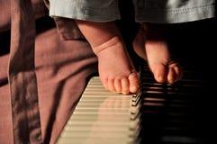 Pés do menino pequeno no piano Imagens de Stock