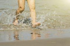 Pés do menino que correm ao longo da praia na água Imagem de Stock