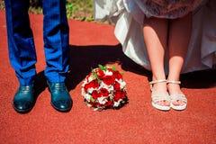 Pés do noivo e da noiva com um ramalhete do casamento Imagens de Stock Royalty Free