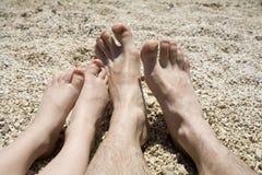 Pés do pai e da criança na praia Imagem de Stock