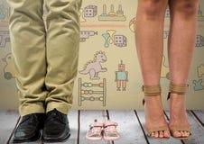 Pés do pai e de mãe com as sandálias das sapatas da criança com gráficos dos brinquedos fotos de stock