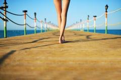 Pés do ` s da jovem mulher em uma ponte no mar imagem de stock