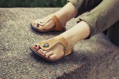 Pés do ` s da mulher em sandálias à moda amarelas do verão Fotos de Stock Royalty Free
