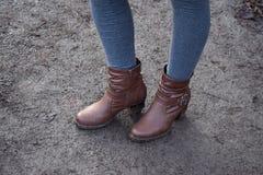 Pés do ` s da mulher nas botas de couro no parque após a chuva Imagens de Stock Royalty Free