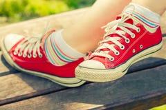 Pés do ` s da mulher nas sapatilhas vermelhas brilhantes da lona Fotografia de Stock
