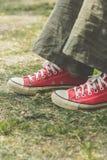 Pés do ` s da mulher nas sapatilhas vermelhas brilhantes da lona Imagens de Stock
