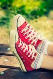 Pés do ` s da mulher nas sapatilhas vermelhas brilhantes da lona Imagem de Stock Royalty Free